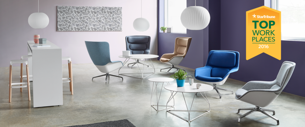 An open and modern lounge featuring several colorful and comfortable chairs, a tall table, several pendant lights, and a graphic piece of art.
