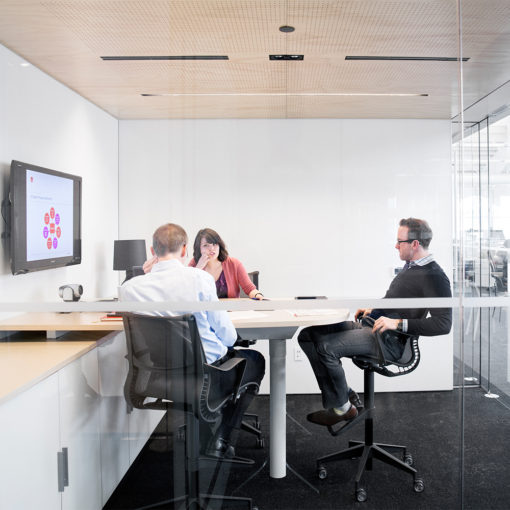 small glass conference room with high table and flexible black office chairs, two men and one woman sitting, TV with presentation on wall, storage cabinets