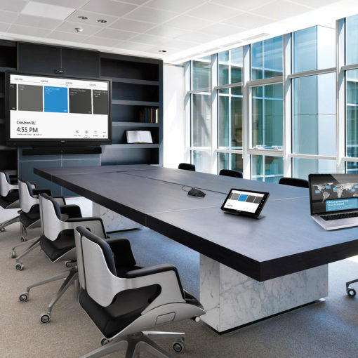 conference room with wall of windows and long black table with white and black office chairs and screen with presentation, conference call devices on table