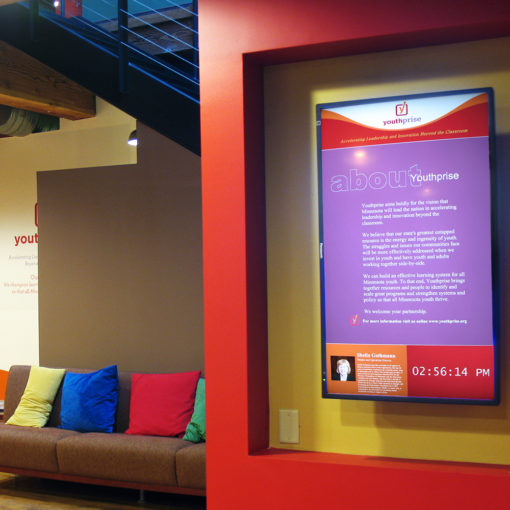 red wall with digital sign featuring purple background and text, bench with colorful pillows in yellow, blue, red, green