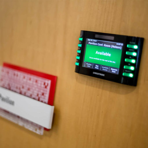 electronic room scheduling device and conference room sign  on wood wall