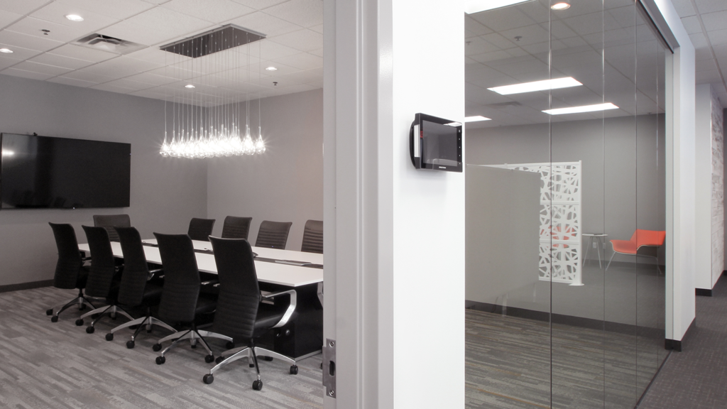 An entry to a conference room featuring a small screen for room reservations.