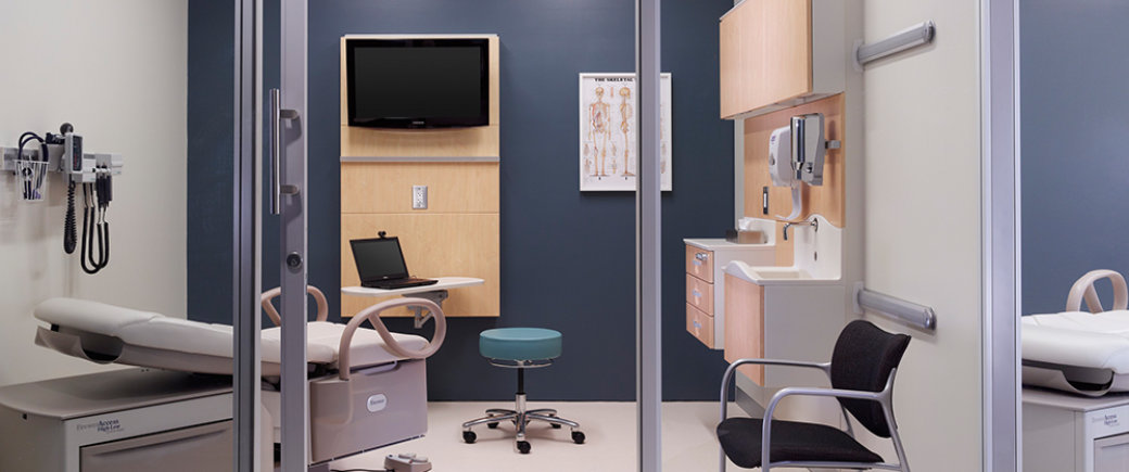 glass-enclosed waiting room at hospital with patient bed, stool and computer, mounted TV, sink station, skeleton chart, and various doctor tools