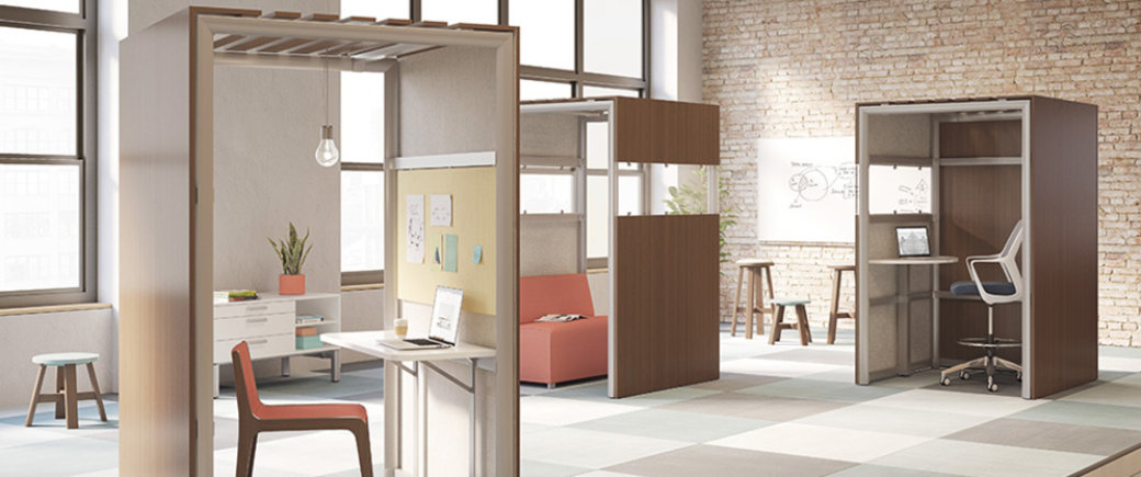 open loft studio with checkered carpet, tall wood single workspaces with desks and chairs of varying heights, salmon colored seats, stools and whiteboard