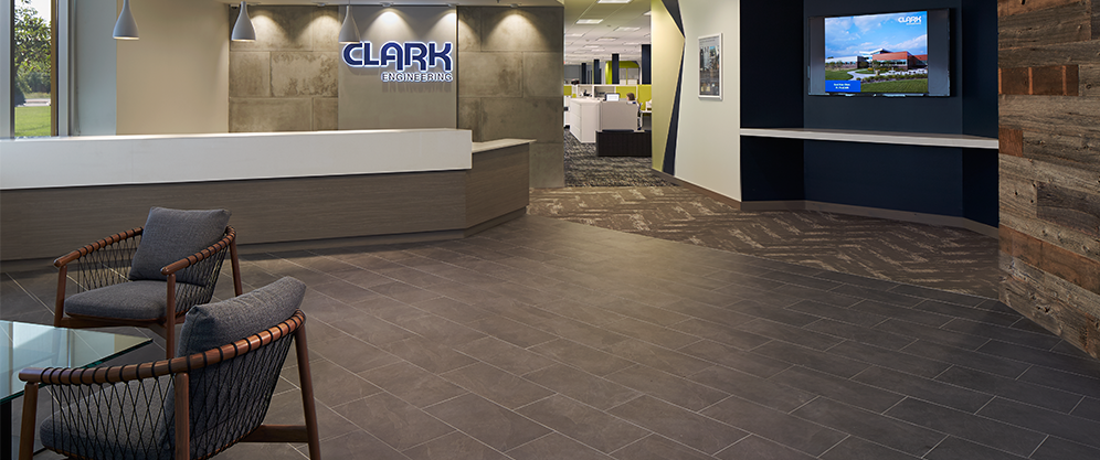 lobby with dark stone tile floors and walls, large desk of wood and white panel, Clark Engineering neon sign, TV, chairs and table, view into desk space