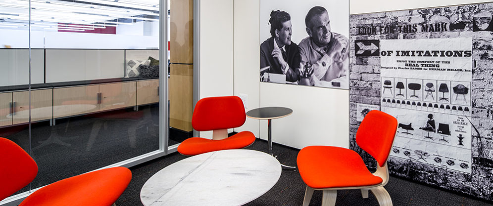 glass conference room with bright red Herman Miller chairs, round marble table, black and white photo of the Eames, poster of Imitation marks for HM