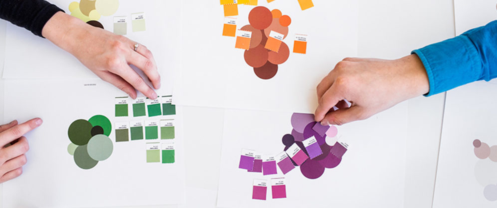female and male hand placing Pantone color swatches in green, purple, yellow, and orange on whiteboard