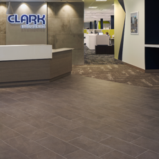 lobby with dark stone tile floors and walls, large desk of wood and white panel, Clark Engineering neon sign, TV, chairs and table, view into desk space Thumbnail