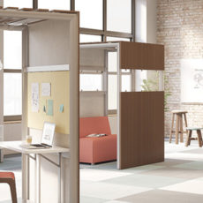 open loft studio with checkered carpet, tall wood single workspaces with desks and chairs of varying heights, salmon colored seats, stools and whiteboard Thumbnail