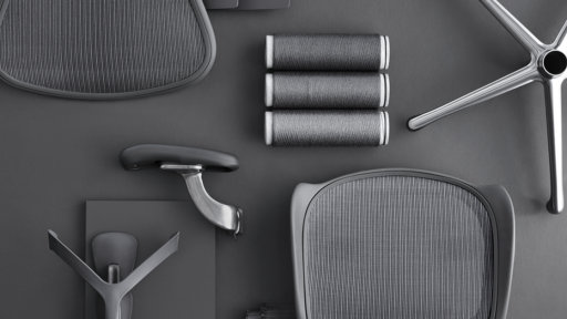 Pieces of a chair, all in grey, are laid out on a dark grey background.