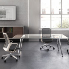 studio office with white brick walls and large windows, storage cabinet, glass top table with chrome tube legs, three black and silver office chairs, TV Thumbnail